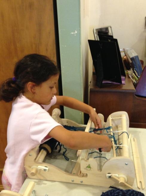2nd grader cutting the warp.