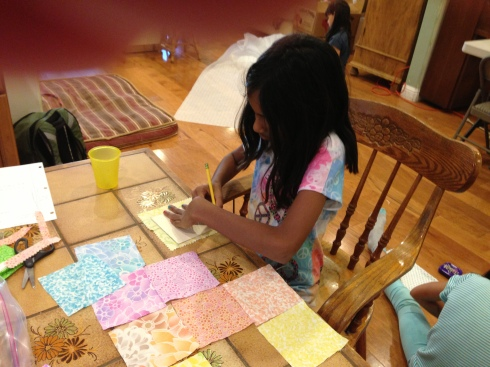 3rd grader deciding how to put her quilt together.
