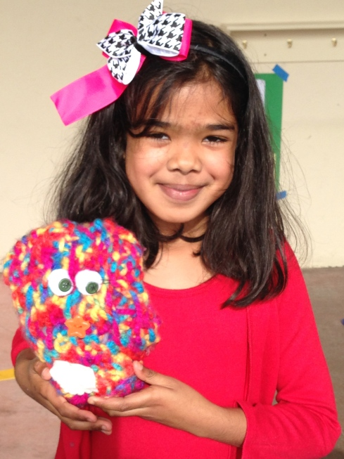 3rd grader with her finished monster stuffie.