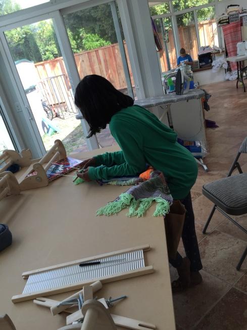 Hem stitching her woven fabric.