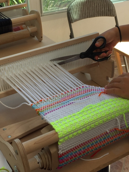 Cutting her sampler off the loom.
